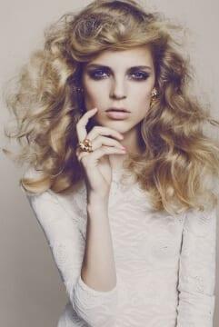 Model i hvid kjole, krøllet hår og smokey eye makeup
